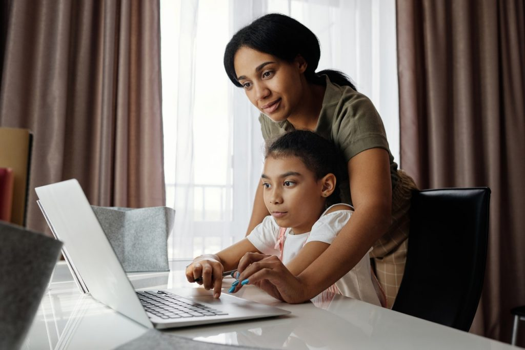 Mother teaching daughter at home, using laptop