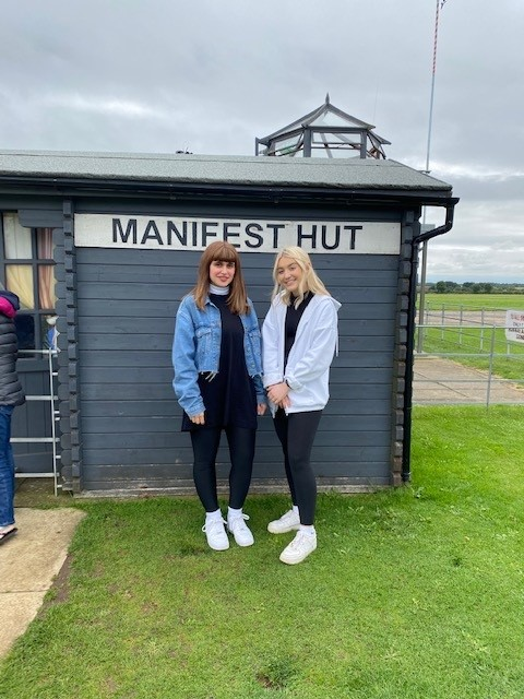 two girls standing infront of manifest hut